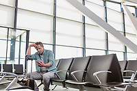Photo of stressed mature man sitting while looking at his phone in airport