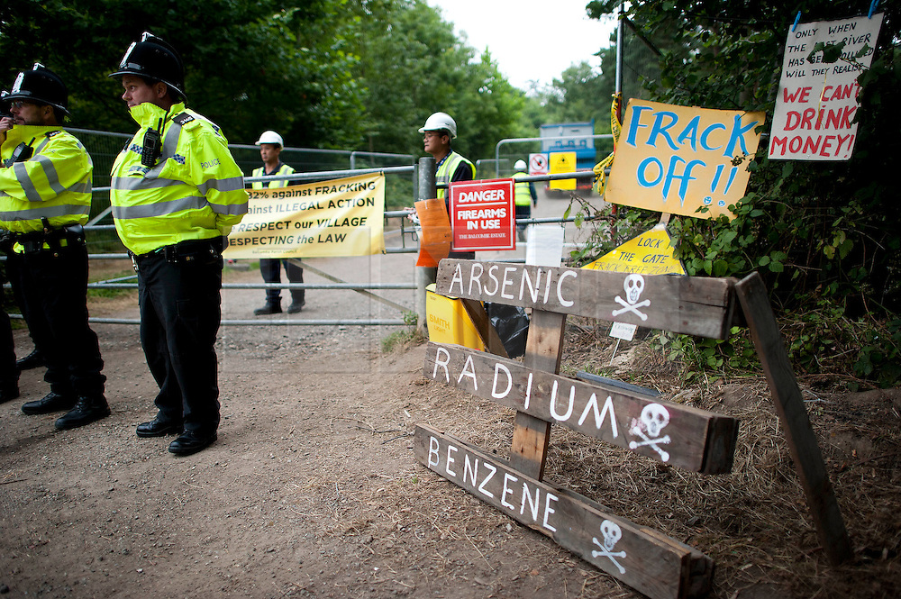 © London News Pictures. 16/08/2013. Balcombe, UK. Police guard the entrance to the Cuadrilla drilling site in Balcombe, West Sussex which has been earmarked for fracking. Cuadrilla has temporarily ceased drilling at the site under advice from the police after campaign group No Dash For Gas threatened a weekend of civil disobedience. Photo credit: Ben Cawthra/LNP