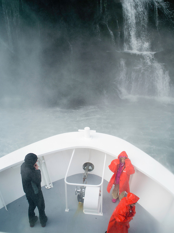 Passengers are drenched by a close encounter with Stirling Falls on a scenic cruise on Milford Sound, Fiordland National Park, New Zealand