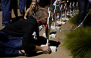 Michael McCabe kisses a photo of Rebecca Wingo, his former girlfriend, at a vigil for the Aurora theater shooting on the 5-year anniversary of the tragedy in Aurora, Colorado United States July 20, 2017.  REUTERS/Rick Wilking