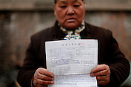 A Chinese petitioner shows a written account of her grievances in hopes to have her case seen by the petitions office in  Beijing, China, Tuesday, March 3, 2009.Widespread frustration with the petition system is simmering and in several recent cases has boiled over, with a handful of people making desperate bids for attention. The peak season for the pilgrimages is the beginning of March, when China's lawmakers gather in the capital for their once-a-year legislative session. In an acknowledgement that the petition system is in crisis, China's Premier Wen Jiabao vowed to improve legal channels for grievances.