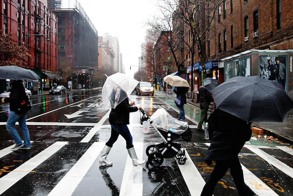 Pedestrian crossing Columbus Avenue in the rain on December 1, 2010 in  New York City.Photo by: Joe Kohen for The Wall Street Journal.