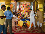 """05 SEPTEMBER 2016 - BANGKOK, THAILAND: A man walks around the statue of Ganesh during the first day of Ganesha Chaturthi celebrations at Shiva Temple in Bangkok. Ganesha Chaturthi also known as Vinayaka Chaturthi, is the Hindu festival celebrated on the day of the re-birth of Lord Ganesha, the son of Shiva and Parvati. The festival, also known as Ganeshotsav (""""Festival of Ganesha"""") is observed in the Hindu calendar month of Bhaadrapada. The date usually falls between 19 August and 20 September. The festival lasts for 10 days, ending on Anant Chaturdashi. Ganesha is a widely worshipped Hindu deity and is revered by many Thai Buddhists. Ganesha is widely revered as the remover of obstacles, the patron of arts and sciences and the deva of intellect and wisdom.      PHOTO BY JACK KURTZ"""