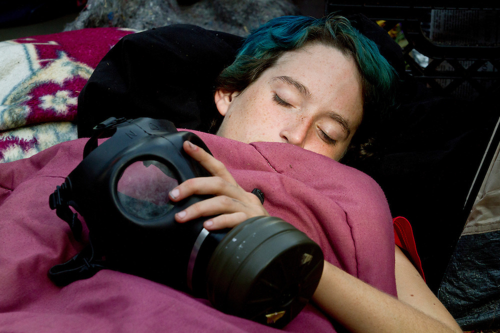 Lucky Sharms sleeps in front of city hall while clutching her gas mask after a long night of demonstrations in Los Angeles, Calif. on Monday, November 28, 2011. (Photo by Gabriel Romero ©2011)