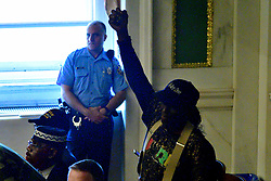 Police officer watches from the side during public testimony by community members and activists on controversial social media posts by officers of the Philadelphia Police Department (PPD) that were unearthed by the Plain View Project, during a council hearing on June 20, 2019 at City Hall in Philadelphia, PA.