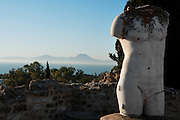 High angle view of the sea with distant mountainous landscape from a terrace of the Villa of the Aviary, with a sculpture of a male torso in the foreground, Carthage, Tunisia, pictured on January 27, 2008, in the morning. Carthage was founded in 814 BC by the Phoenicians who fought three Punic Wars against the Romans over this immensely important Mediterranean harbour. The Romans finally conquered the city in 146 BC. Subsequently it was conquered by the Vandals and the Byzantine Empire. Today the site is a UNESCO World Heritage. The Roman Villa of the Aviary, with its octagonal garden set in a peristyle courtyard, is known for its fine mosaics depicting birds. Picture by Manuel Cohen.