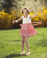 Young girl using hula hoop in a park