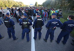 © London News Pictures. Hungarian police try to contain migrants as they broke out from the camp and joined the motorway and started walking towards Budapest close to the Hungarian and Serbian border town of Roszke, Hungary, September 7 2015. The UN's humanitarian agencies are on the verge of bankruptcy and unable to meet the basic needs of millions of people because of the size of the refugee crisis in the Middle East, Africa and Europe, senior figures within the UN have told the media.  Photo credit: Paul Hackett/LNP