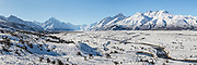 A large panoramic of the braided Tasman River winding along the frozen delta surface extending south of Mount Cook and its surrounding snowy mountain ranges.