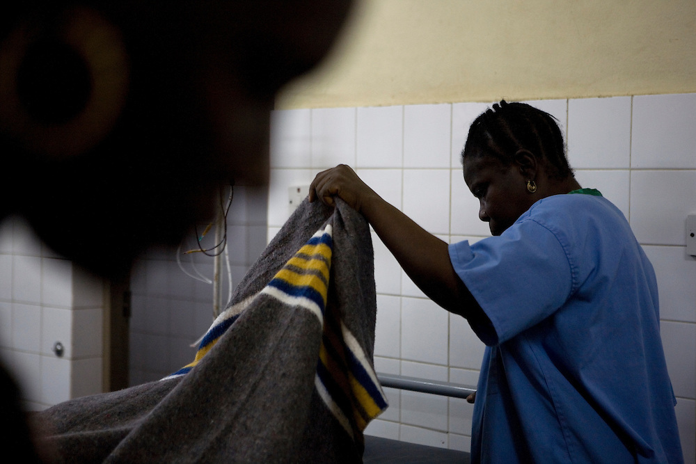 Midwife Hawa covers Mommy's body. Mommy delivered and died from postpartum bleeding at the PCMH (Princess Christian Memorial Hospital). Freetown, Sierra leone.