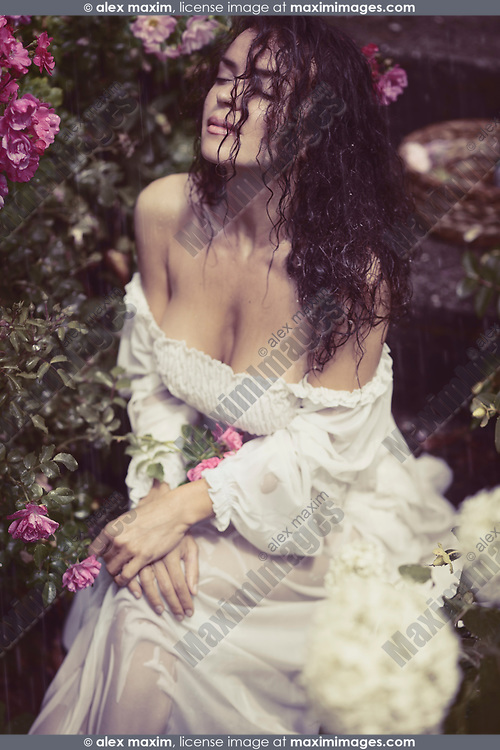 Romantic sensual portrait of a beautiful sexy young woman with wet dark hair and wet summer dress sitting alone in the rain in a rose garden