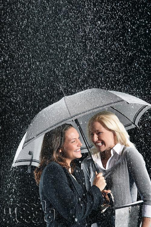 Smiling Businesswomen Standing Under Umbrella together during rain