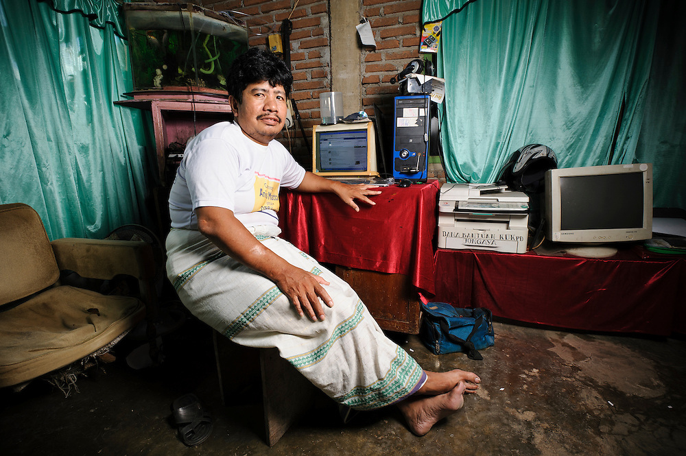 Bapak Mursalim at his home in the Jongaya leprosy settlement, Makassar, Sulawesi, Indonesia. Bapak Mursalim, 41, discovered he had leprosy when he was still in elementary school and has lived in Jongaya leprosy settlement since 1997.  He met his wife Ibu Intan, 43, at the Daya leprosy hospital whilst they were both receiving treatment for the disease and they married in 1998.  Bapak Mursalim works as an ojek motorbike taxi driver, but also runs a small computer and photocopy business from his home.  He volunteers with Permata and runs the organisation's facebook page and website.