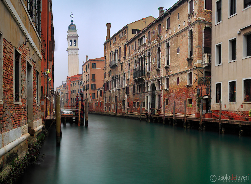 A view of Rio dei Greci (Greeks' Canal) with the leaning bell tower of the orthodox church of San Giorgio dei Greci in the background. Taken on a misty early morning of mif January, this is stitched from four vertical frames.