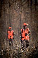 MALE AND FEMALE HUNTER WEARING BLAZE ORANGE WALKING TOGETHER THROUGH A CORN FIELD