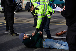 "© Licensed to London News Pictures. 19/11/2016. Heathrow, UK. An activist being arrested by police after being removed form a road surface. A group of activists stage attach themselves to a road surrounding  Heathrow Airport, during a demonstration against the expansion of Heathrow Airport and the building of a third runway. Some activists  threatened ""direct action"". Photo credit: Ben Cawthra/LNP"