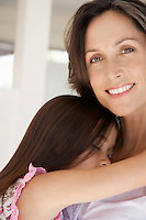 Mother cuddling sleeping daughter head and shoulders