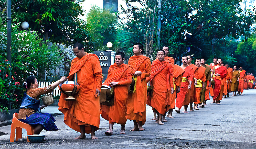 Buddhist monks walking the streets of Luang Prabang early in the morning receiving alms.