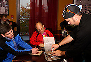 Matt Lindsay of Oakwood (left) watches Andy Williamson, captain of team Mo Fro (right) put the first ceremonial cash in the donation box following the Dayton Movember Mustache Ride to benefit men's cancer awareness and research through downtown Dayton on First Friday, November 4, 2011.