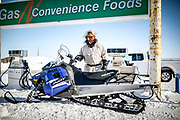A man fills up his snowmobile at a gas station in Tuktoyaktuk.