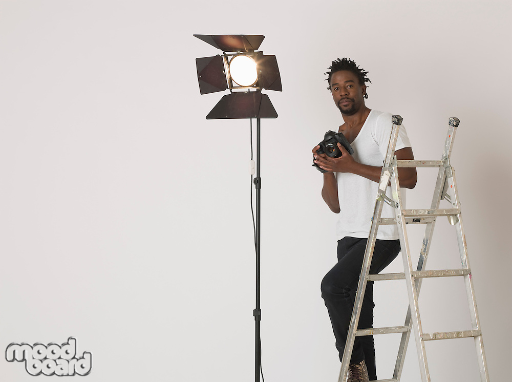 Mid adult (30-35 years) photographer in studio