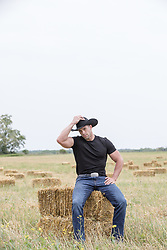 cowboy sitting on a hay bale in a field