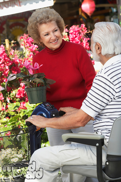 Senior woman talking with elderly man on motor scooter in garden center