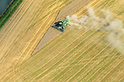 Nederland, Flevoland, Gemeente Dronten, 27-08-2013; maaien en dorsen van het graan met een John Deere combine veroorzaakt een stofwolk, ten noordoosten van Biddinghuizen.<br /> A John Deere combine causes a cloud of dust while mowing and grain threshing in the polder near Biddinghuizen.<br /> luchtfoto (toeslag op standaard tarieven);<br /> aerial photo (additional fee required);<br /> copyright foto/photo Siebe Swart.