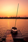 Image of a sailboat at sunrise from across the bay at Mystic Seaport, Connecticut, American Northeast