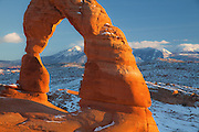 The iconic Delicate Arch with a warm glow from a winter sunset in Arches National Park, Utah.