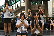 Schoolgirls in Bangkok pray at a shrine outside Central World, one of the city's iconic shopping malls.