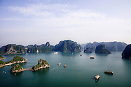 Limestone's landscape of Halong bay with few boats sailing on the sea. Vietnam, Asia
