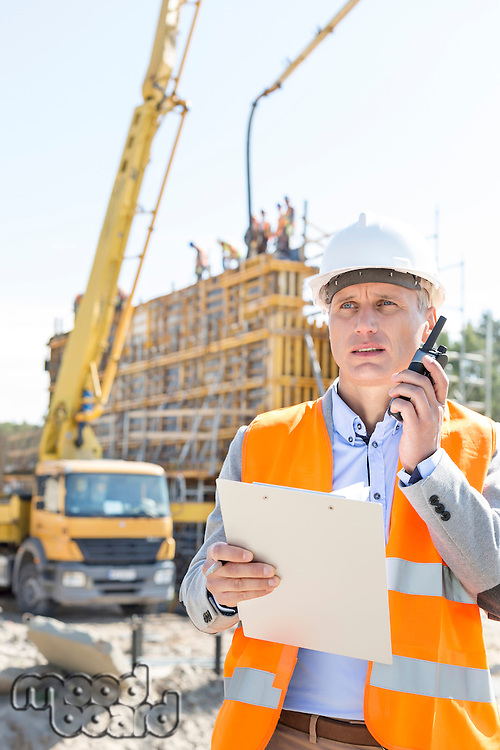 Male supervisor using walkie-talkie while holding clipboard at construction site