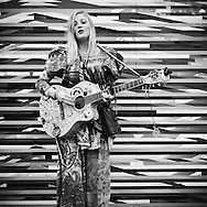 Young woman in Amsterdam wearing hippy style colorful clothes performing with guitar playing and singing in front of a highly decorated wall
