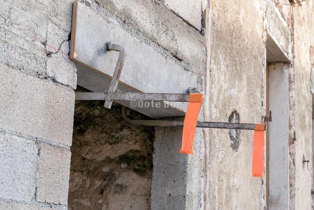 clamps with orange warning tape at a concrete and stone window opening  under construction