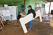 24 JANUARY 2010 -- WENDEN, AZ: Felipe Cruz carried a headboard out of a family member's home in Wenden.  Wenden was slammed by its second 100 year flood in 10 years on Thursday night when water raced through Centennial Wash and into the small town in La Paz County west of Phoenix. Most of the town's residents were evacuated to Red Cross shelters in Salome, about 5 miles west of Wenden.   PHOTO BY JACK KURTZ
