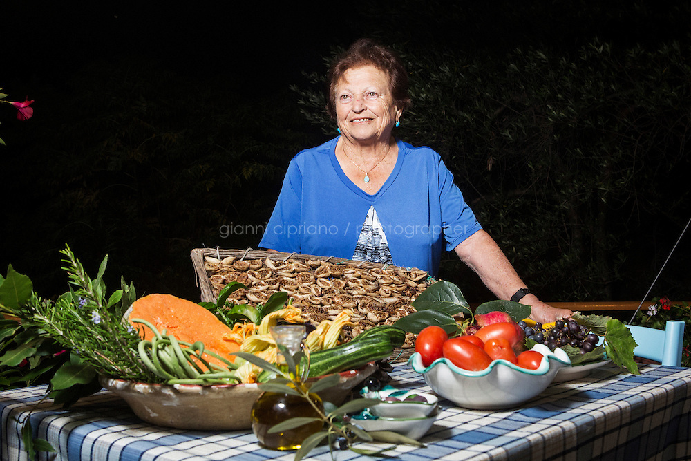 PIOPPI (POLLICA), ITALY - 5 OCTOBER 2016: Delia Morinelli (79) poses for a portrait in front of local vegetables, fruits and olive oil in the terrace of her home, which recently opened to the public for lunch and dinner in Pioppi, a hamlet in the municipality of Pollica, Italy, on October 5th 2016. Starting in the 60's, Delia Morinelli was the cook of Ancel Keys, the American scientist who studied the influence of diet on health and the promoter of the Mediterranean Diet.<br /> <br /> To understand how people can live longer throughout the world, researchers at University of California, San Diego School of Medicine have teamed up with colleagues at University of Rome La Sapienza to study a group of 300 citizens, all over 100 years old, living in Acciaroli (Pollica), a remote Italian village nestled between the ocean and mountains in Cilento, southern Italy.<br /> <br /> About 1-in-60 of the area&rsquo;s inhabitants are older than 90, according to the researchers. Such a concentration rivals that of other so-called blue zones, like Sardinia and Okinawa, which have unusually large percentages of very old people. In the 2010 census, about 1-in-163 Americans were 90 or older.