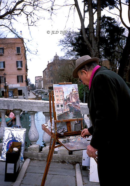 Man wearing fedora hat and overcoat painting a scenic picture in Venice, near Giardini, on the via Garibaldi.  He is absorbed in his task, mixing a color.  View shows a palazzo and hump backed foot bridge.  Two shopping bags, filled, stand near the easel.