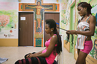 COMO, ITALY - 21 JUNE 2017: Sandra Obodo (left), 26), a Nigerian migrant, is seen here as one friend braids her hair  in the center ran by priest Giusto della Valle in Como, Italy, on June 21st 2017. Ms. Obodo said she crossed over from Libya nine months ago after escaping retribution murders at home and that a second boat she departed with was lost at sea.<br /> <br /> Residents of Como are worried that funds redirected to migrants deprived the town's handicapped of services and complained that any protest prompted accusations of racism.<br /> <br /> Throughout Italy, run-off mayoral elections on Sunday will be considered bellwethers for upcoming national elections and immigration has again emerged as a burning issue.<br /> <br /> Italy has registered more than 70,000 migrants this year, 27 percent more than it did by this time in 2016, when a record 181,000 migrants arrived. Waves of migrants continue to make the perilous, and often fatal, crossing to southern Italy from Africa, South Asia and the Middle East, seeing Italy as the gateway to Europe.<br /> <br /> While migrants spoke of their appreciation of Italy's humanitarian efforts to save them from the Mediterranean Sea, they also expressed exhaustion with the country's intricate web of permits and papers and European rules that required them to stay in the country that first documented them.