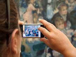 Taking a digital photo of a Renoir painting at the Musee D'Orsay, Paris.