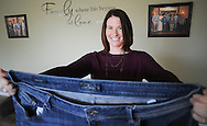 Janessa McCracken, 35, of Lower Salford holds up a pair of jeans she wore when she weighed 300 pounds as she speaks about the bariatric surgery that she had one year ago that helps her lose 150 pounds Thursday, November 17, 2016 in Lower Salford, Pennsylvania. (Photo by William Thomas Cain)
