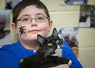 Wantagh, New York, USA. February 5, 2017.  AYDIN SHAH, 8 1/2, of Merrick is holding SALSA, a 5 1/2 month old female kitten available for adoption at Last Hope Animal Rescue's Open House during Hallmark Channel's Kitten Bowl IV. Aydin had a black spider painted on his face during the party. Kittens in Last Hope Lions team played against kittens in North Shore Bengals team. Last Hope kittens have been part of each Kitten Bowl, whose purpose is to promote cat and kitten adoptions.