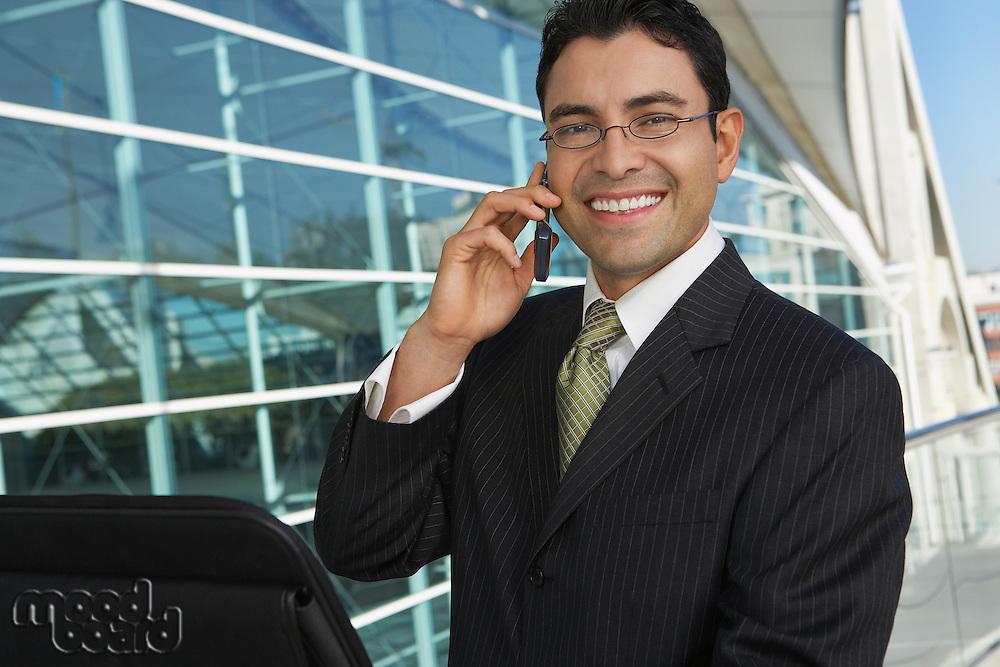 Businessman using mobile phone outside office building, portrait