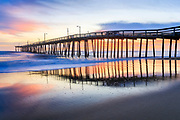 Nags Head Fishing Pier at sunrise reflected in the wet sand beach on the Outer Banks of NC.
