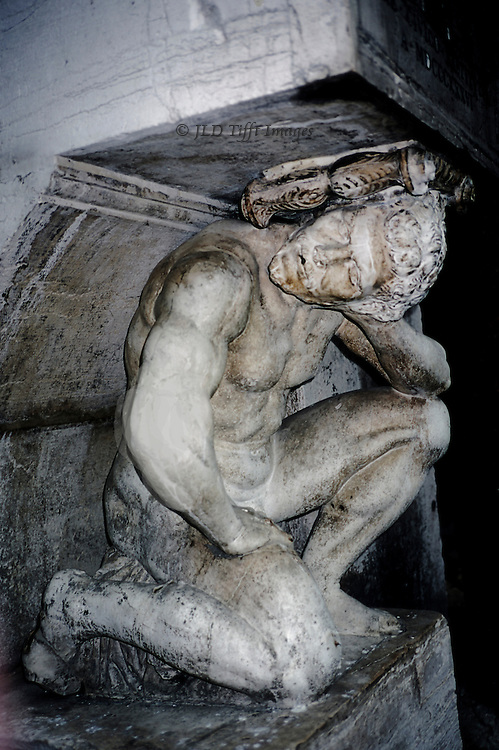 Close up of the crouching hunchback granite figure near the Rialto Bridge, in Venice.  His head is bowed and turned to one side under the weight he bears.  Facial expression shows pain and neck seems about to break.