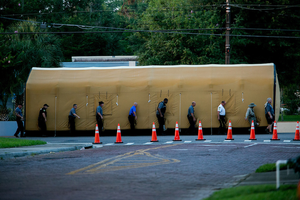 ORLANDO - JUNE 14, 2016: With sweltering temperatures in Orlando, law enforcement officers carry a cooling tent near the scene of the mass shooting that took place at Pulse nightclub in Orlando, Florida. CREDIT: Sam Hodgson for The New York Times.