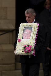 © Licensed to London News Pictures . 30/08/2012 . Manchester, UK . The funeral of Winnie Johnson . A funeral director carries a tribute bearing Winnie's face . Moors Murderer Ian Brady and Myra Hindley murdered Johnson 's 12 year old son Keith Bennett . Winnie Johnson dedicated her life to finding her son's body . Photo credit : Joel Goodman/LNP