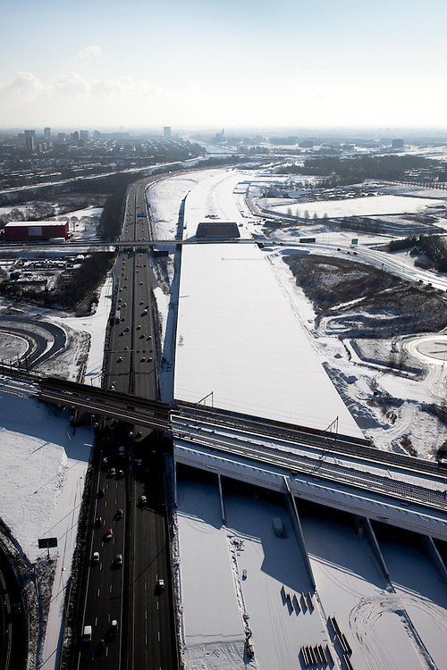 Nederland, Utrecht, Leidsche Rijn, 31-01-2010; de ingang van de nieuwe landtunnel voor de A2, met vier tunnelbuizen. De tunnel ligt parallel aan de bestaande A2, het asfalt zal op termijn verdwijnen. Op het dak van de tunnel zal een park komen. Links het Amsterdam-Rijnkanaal, skyline Utrecht aan de horizon. De verbreedde spoorlijn Utrecht-Gouda gaat over de ingang tunnelbuizen..Entrance of the new landtunnel for A2, with four tunnel tubes. The tunnel lies parallel to the existing A2, the asphalt will eventually disappear. The roof of the tunnel will be a park. Left the Amsterdam-Rhine Canal, Utrecht skyline on the horizon. The broadened railway line Utrecht-Gouda above the entrance tunnel tubes (foreground).luchtfoto (toeslag), aerial photo (additional fee required).foto/photo Siebe Swart