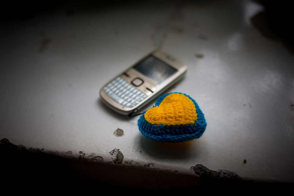 """Olesya's cell phone with a small heart attached, with the colours of Ukraine. """"When I was in the ambulance, I thought I was living my last minutes. I sent a message with my phone on Twitter saying """"Я вмираю"""" [I'm dying]. I wanted the boy I like, and also my loved ones, to know that my thoughts was for them at that moment"""" she told during the interview."""