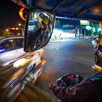 Jan 5, 2013 - A tuk tuk driver navigates the traffic in the Cambodian capital city of Phnom Penh. <br /> <br /> Story Summary: Amidst the feverish pace of Phnom Penh&rsquo; city streets, a workhorse of transportation for people and goods emerges: Bicycles, motorcycles, scooters, Mopeds, motodups and Tuk Tuks roam in place of cars and trucks. Almost 90 percent of the vehicles roaming the Cambodian capital of almost 2.3 million people choose these for getting about. Congestion and environment both benefit from the small size and small engines. Business is booming in the movement of goods and and another one million annual tourists in Cambodia&rsquo;s moto culture.